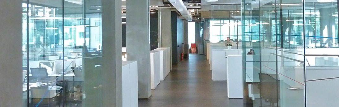 Das Bild zeigt ein modernes Büro mit Glas und Beton, das jedoch eine ausgefeilte Raumakustik besitzt und somit ein entspanntes Arbeiten möglich ist und die die Diskretion von Gesprächen unterstützt.