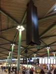Das Bild zeigt ein dreieckiges Lautsprechergehäuse, das von der Hallendecke abgependelt ist. Es hat die Höhe von circa 5 Metern und seine Seitenlänge von circa 120 cm.