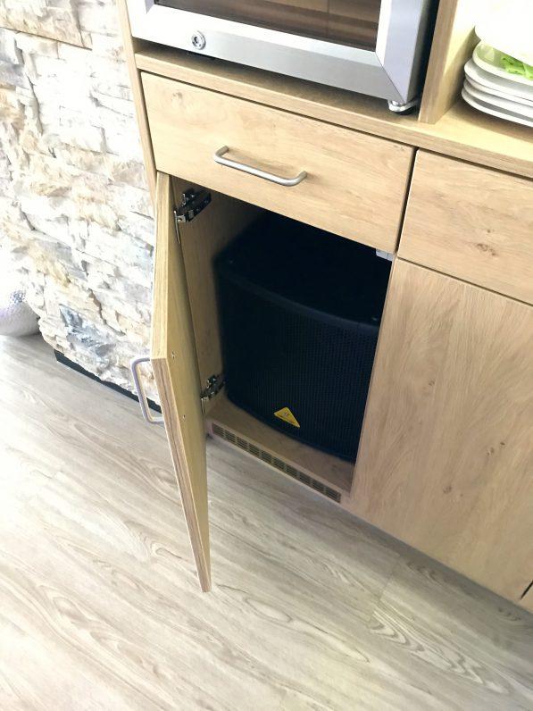 Das Bild zeigt einen Subwoofer Lautsprecher, der in einem Schrank, hinter einer massiven Türe eingebaut ist.