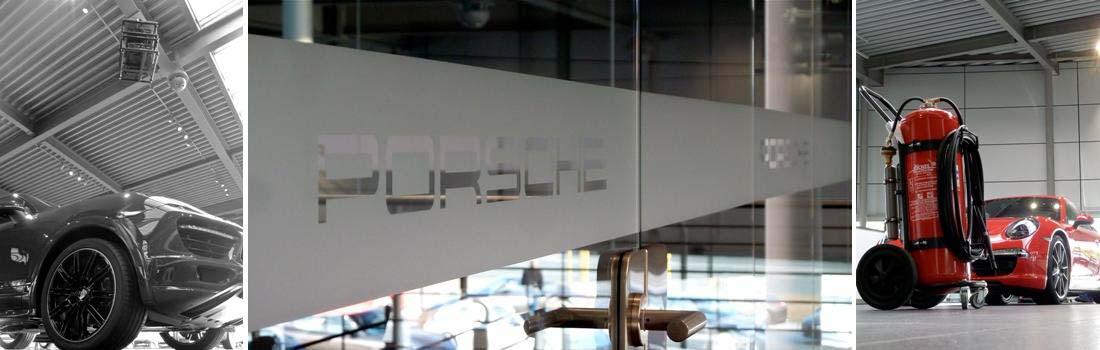 Das Bild zeigt eine Collage zum Projekt Porsche Zentrum Nürnberg. In der Mitte ist der Schriftzug Porsche auf eine große Glasfläche satiniert. Links ist ein neuer SUV der Marke zu sehen, mit Perspektive zum Projektor-Stack an der Decke. Rechts ist ein neuer, feuerroter Sportwagen im Hintergrund zu sehen. Im Vordergrund steht ein roter Feuerlöscher, der perspektivisch mit dem Sportwagen verschmilzt.