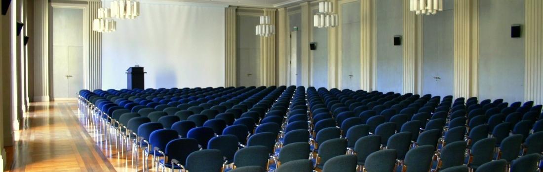 Das Bild zeigt den großen Saal der Akademie der Wissenschaften in München. An der Stirnseite ist ein Rednerpult mit Großprojektion zu sehen. Die dezentrale Lautsprecheranordnung bietet eine sehr gute Sprachverständlichkeit.