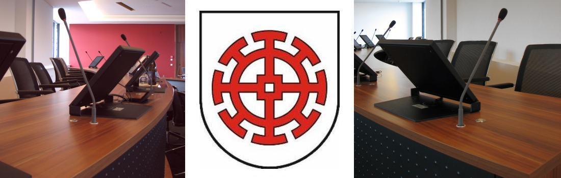 Das Bild zeigt eine Collage des Projekts Landratsamt Mühldorf. Links und rechts sind die Konferenzmikrofone zu sehen, jeweils vom jeweiligen Tischende aus. In der Mitte ist das Gemeindewappen zu sehen.