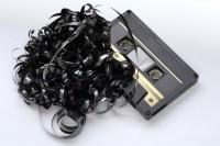 Das Bild zeigt eine schwarze Audiokassette mit Bandsalat.